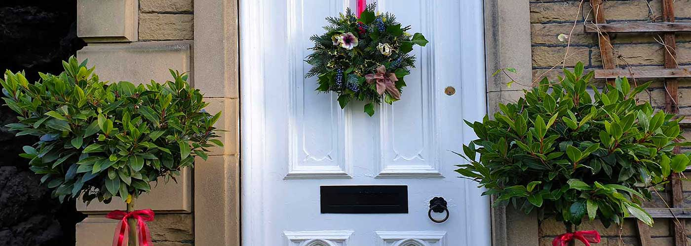 Christmas wreath on white front door in Derbyshire