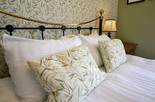Double bedroom with brass beadstead and cushions