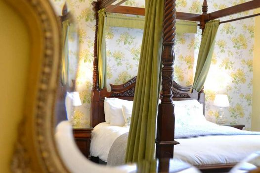 Four-poster bed reflection in mirror
