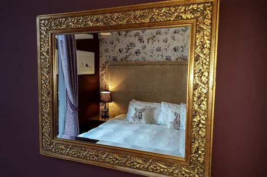 Gold mirror reflecting double or twin bedroom