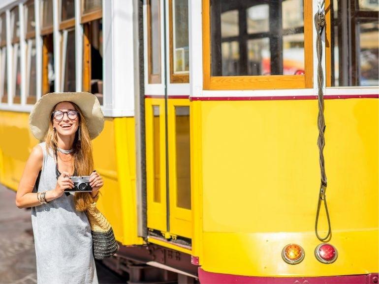 Woman beside yellow tram
