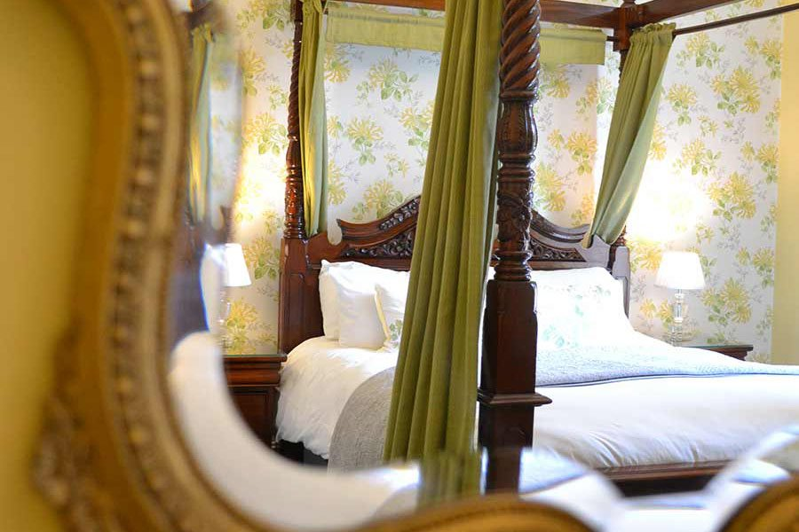 Reflection of four poster bed in mirror