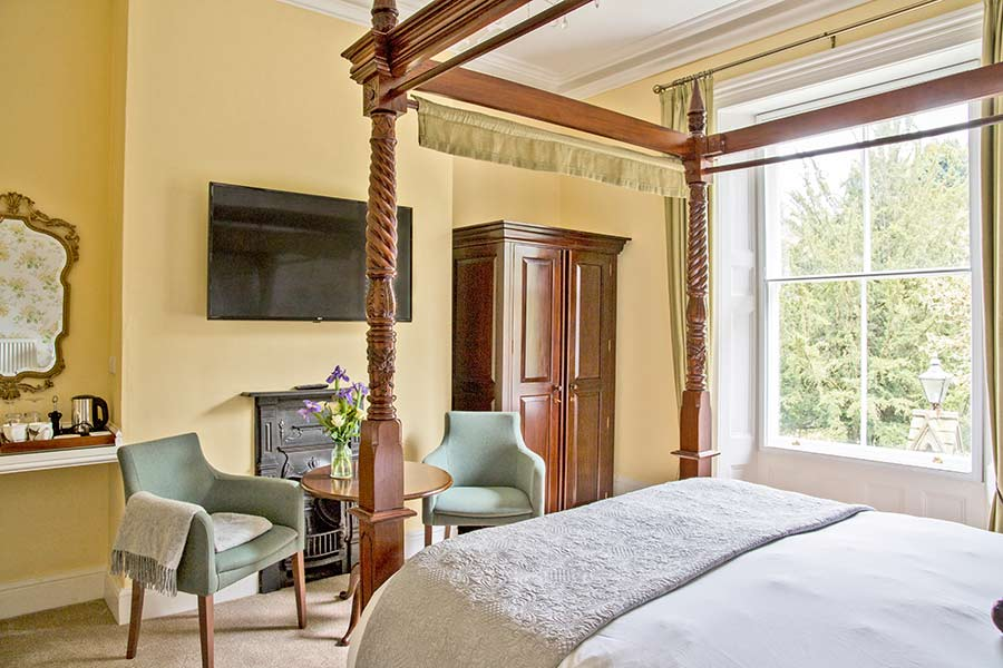 Seating area at foot of four poster bed